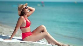 Aanbiddelijke sexy maniervrouw in het rode zwempak genieten die zitting op zandstrand zonnebaden stock footage