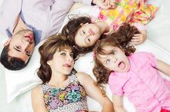 Aanbiddelijke Spaanse familie die met hoofden liggen stock foto
