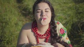 Aanbiddelijke te zware vrouwenzitting in gras die smakelijke reuzel snuiven die voorbereidingen treffen te eten Traditiesconcept, stock footage