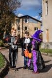 Aanbiddelijke truc drie of treaters die voor het suikergoed van Halloween bedelen Royalty-vrije Stock Foto's