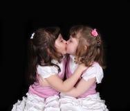 Aanbiddelijke tweelingen die op zwarte omhelzen Stock Foto's
