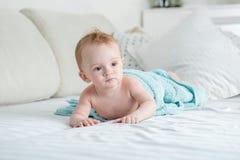 Aanbiddelijke 9 van de babymaanden oud jongen die op bed onder grote blauwe handdoek na het hebben van bad liggen Royalty-vrije Stock Foto