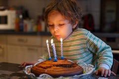 Aanbiddelijke vier éénjarigenjongen die zijn verjaardag en het blazen vieren Royalty-vrije Stock Foto's