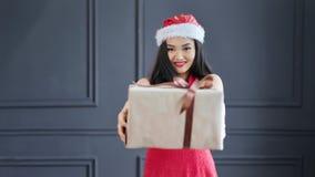 Aanbiddelijke vrouwelijke Santa Claus geeft grote giftdoos in Kerstmistijd bij studio middelgroot schot