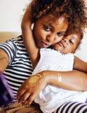 Aanbiddelijke zoete jonge Afro-Amerikaanse moeder met leuk weinig dochter, die hebbend pret het speel glimlachen thuis hangen stock afbeelding
