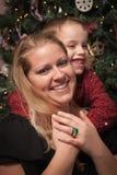 Aanbiddelijke Zoon die Zijn Mamma in Front Of Christmas Tree koesteren Royalty-vrije Stock Afbeelding