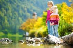 Aanbiddelijke zusters die door Hallstatter See meer in Oostenrijk op warme de zomerdag spelen De leuke kinderen die pret bespatte royalty-vrije stock afbeelding