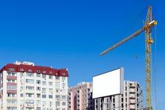In aanbouw bouwend kraan tegen de achtergrond van een gebouw met meerdere verdiepingen De reclame van aanplakbord met exemplaarru royalty-vrije stock afbeeldingen