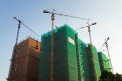 In aanbouw bouwend met gebeëindigde gebouwde gebouwen Stock Foto's