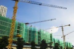 In aanbouw gebouwen met kranen die aan blauwe hemel werken Royalty-vrije Stock Foto