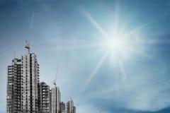 In aanbouw gebouwen met torenkraan op blauwe hemel met heldere zon Stock Foto