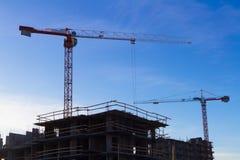 In aanbouw high-rise de bouw met twee kranen de achtergrond van blauwe hemel Stock Afbeelding
