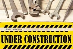 In aanbouw raad met reparatiehulpmiddelen Moersleutel op houten achtergrond Royalty-vrije Stock Fotografie