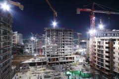 In aanbouw verlichtend gebouwen met meerdere verdiepingen en kranen Royalty-vrije Stock Afbeeldingen
