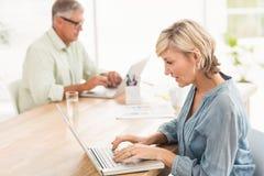 Aandachtig commercieel team die aan laptops werken stock foto's