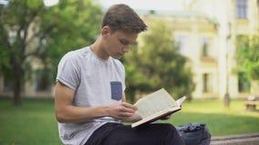 Aandachtig het avonturenboek van de tienerlezing op bank in park, intellectuele hobby stock footage