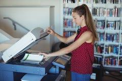 Aandachtig schoolmeisje die Xerox-fotokopieerapparaat in bibliotheek met behulp van stock foto