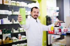 Aandachtige apotheker die nuttige drug voorstellen royalty-vrije stock afbeelding