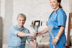 Aandachtige ijverige verpleegster die haar patiënt pekelen de steunpilaren stock afbeeldingen