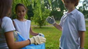 Aandachtige jonge vrijwilligers die terwijl het houden van park schoon samenwerken stock videobeelden