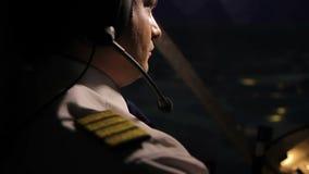 Aandachtige kapitein proef in hoofdtelefoon die reusachtig lijnvliegtuig navigeren bij nacht, baanplichten stock video