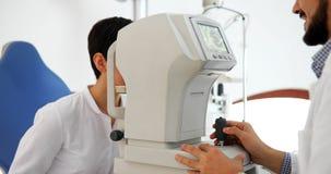 Aandachtige optometrist die vrouwelijke patiënt op spleetlamp onderzoeken stock afbeelding