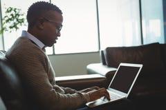 Aandachtige uitvoerende gebruikende laptop Royalty-vrije Stock Afbeeldingen