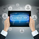 AANDEELHOUDERSwoord op tabletpc door zakenmanhanden die wordt gehouden stock fotografie