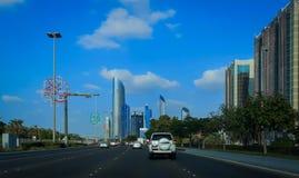 Aandrijving in Abu Dhabi-stads corniche weg met mening van beroemde torens tegen blauwe hemel en wolken stock afbeelding