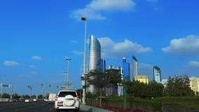 Aandrijving in Abu Dhabi-weg van stads de beroemde corniche met mening van moderne wolkenkrabbers tegen blauwe hemel en wolken stock video