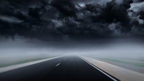 Aandrijving bij lege asfaltweg aan onweersbui door mist royalty-vrije stock afbeelding