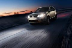 Aandrijving van de auto de snelle snelheid op asfaltweg bij schemer Royalty-vrije Stock Fotografie