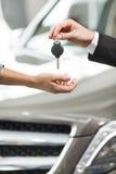 Aandrijving zorgvuldig! Close-upspruit van de hand van de autoverkoper het geven Royalty-vrije Stock Fotografie