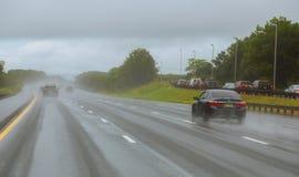 Aandrijvingsauto in regen op asfalt natte weg Auto's het verkeerslicht Royalty-vrije Stock Fotografie
