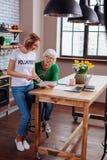 Aangename maatschappelijk werker die potlood overgaan tot bejaarde voor het ondertekenen royalty-vrije stock fotografie
