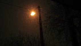Aangestoken Lamp die bij Nacht en Sneeuwdalingen verschijnen stock video