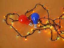 Aangestoken lantaarns voor verlichting, bollen rood en blauw op een heldere gele achtergrond, hoogste mening stock foto