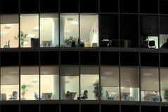 Aangestoken vensters van verlaten bureau bij nacht Royalty-vrije Stock Foto's