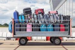 Aanhangwagen op luchthaven met koffers wordt gevuld die royalty-vrije stock afbeeldingen