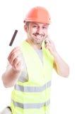 Aannemer die op telefoon spreken en creditcard houden stock foto's