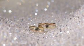Aanpassend huwelijks gouden banden in drie die kleuren op een opzichtige die achtergrond worden geplaatst uit kristalparels wordt Royalty-vrije Stock Fotografie