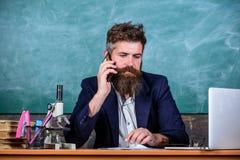 In aanraking met school Schoolhoofd of leraar die ouders roepen om over examenresultaten te rapporteren Mens met baardbespreking stock fotografie