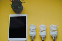 Aanrakingsstootkussen ipad en Energie - het concept van besparings gloeilampen Royalty-vrije Stock Foto's