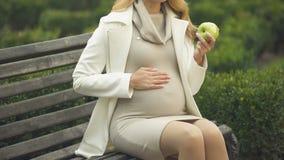 Aanstaande moeder die appel eten en zacht buik, moederschapsliefde, zorg strijken stock footage