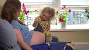 Aanstaande moeder en haar mooie dochter die met babyhoed spelen op vrouwenbuik stock footage