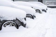 Aantal geparkeerd die auto's met sneeuw, mening van de voorwielkap en bumper een rommel van worden gemaakt van royalty-vrije stock foto