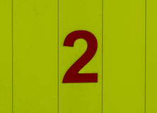 Aantal twee, rood, plaatste tegen helder geel hout Royalty-vrije Stock Foto's