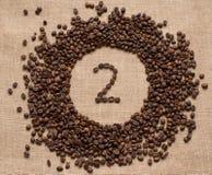 Aantallen koffiebonen op juteachtergrond stock foto's