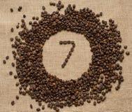 Aantallen koffiebonen op juteachtergrond Stock Afbeeldingen