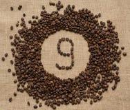 Aantallen koffiebonen op juteachtergrond stock foto